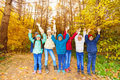Kids group with arms up standing in row together the air during autumn daytime Stock Photo