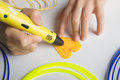 Kids hand holding yellow 3D printing pen with filaments and makes heart..