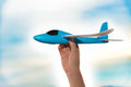 Kids hand lifting up a blue airplane model Royalty Free Stock Photo