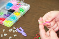 Kids hands creating bracelet with rubber bands and box in the ba background Royalty Free Stock Image