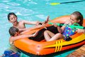 Kids having fun with water gun children in outdoor swimming pool games Stock Photos