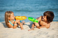 Kids having fun with water pistols on the beach playing in sand Stock Images