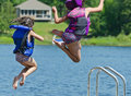 Kids having summer fun  jumping off dock into lake Royalty Free Stock Photo