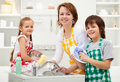 Kids helping their mother in the kitchen washing dishes together Stock Photos