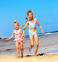 Kids holding hands running on  beach. Stock Photo