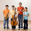 Kids holding saxophone, cello, flute and clarinet Royalty Free Stock Photo