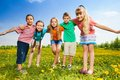 Kids hugging standing in the field five happy together dandelion Stock Images