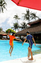 Kids jumping into resort pool Royalty Free Stock Photography