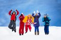 Kids jumping in snow group of five happy with lifted hands Royalty Free Stock Photo