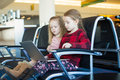 Kids with a laptop at the airport while waiting his flight little girls Royalty Free Stock Images