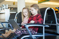 Kids with a laptop at the airport while waiting little girls his flight Royalty Free Stock Photo
