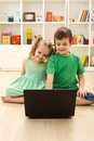 Kids with laptop, sitting on the floor Royalty Free Stock Photo