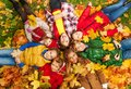 Kids lay on the autumn grass large group of laying in with maple leaves all over them day Stock Photo