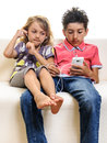 Kids listening music smartphone two children girl and boy big brother on sofa with mobile cell phone isolated on white Royalty Free Stock Photography