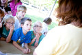 Kids listening to a presentation outside group of attentive elementary school aged children learning at an educational booth about Royalty Free Stock Image