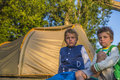 Kids looking at sunset two boys sitting in front of a tent the Royalty Free Stock Photos