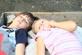 Kids lying on carriage little boy and girl sacks in and having rest Royalty Free Stock Photography