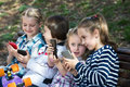 Kids with mobile devices outdoor happy children sitting on bench and playing Royalty Free Stock Photo
