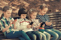 Kids with mobile devices outdoor positive sitting on bench in street Royalty Free Stock Image