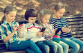 Kids with mobile devices outdoor positive sitting on bench in street Stock Photos