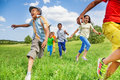 Kids in motion of running on green field Royalty Free Stock Photo