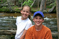 Kids by a mountain river boy and girl posing and smiling near stream near grand lake co on the western side of rocky national park Stock Photos
