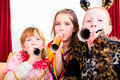 Kids with noisemakers making noise on party looking into the camera Stock Image