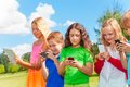 Kids occupied with phone five happy stnading phones and digital devices Stock Photography