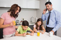 Kids with parents having breakfast in kitchen young the at home Stock Photo