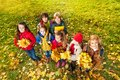 Kids in the park on autumn lawn group of standing with maple yellow leaves bouquet casual clothes Royalty Free Stock Photography
