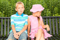 Kids in a park two cute sitting on bench the girl looking away indifferently and the boy showing intense emotion Royalty Free Stock Images