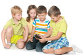Kids plaing with a new gadget group of four are playing Royalty Free Stock Photo