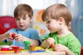 Kids with play clay at home playing or kindergarten or playschool Royalty Free Stock Images
