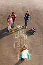 Kids play hopscotch group of jumping on the game drawn on the asphalt after school wearing autumn clothes Royalty Free Stock Image