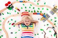 Child with toy train. Kids wooden railway. Royalty Free Stock Photo