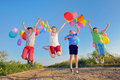Kids playing with balloons on field Stock Photography