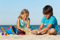 Kids playing on the beach building sand castle a decorating it with seashells Stock Photo