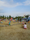 Kids playing in the big sandbox in sochi park russia children summertime blue sky with white clouds Royalty Free Stock Photo