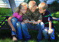 Kids playing on cell phone three happy young sitting together in a yard looking at or games a shallow depth of field Stock Photo