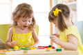 Kids playing with colorful block toys. Two children girls at home or daycare center. Educational child toys for preschool and kind