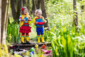 Kids playing with colorful paper boats in a park children play small river on sunny spring day exploring the nature brother and Royalty Free Stock Photo