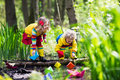 Kids playing with colorful paper boats in a park children play small river on sunny spring day exploring the nature brother and Royalty Free Stock Images