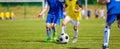 Kids playing football soccer game on sports field. Boys kicking