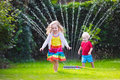 Kids Playing With Garden Sprin...