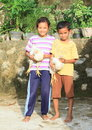 Kids playing with hens barefoot girl and boy in labuan bajo flores indonesia Stock Image