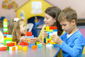 Kids playing at kindergarten with plastic building blocks Stock Photo