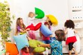 Kids playing pillow fight large group of actively with in the living room on the coach Royalty Free Stock Photos