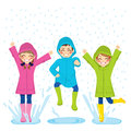 Kids playing on puddles little wearing colorful raincoats and boots Stock Photography