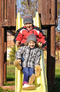 Kids playing on slide in park at children playground boy and girl Royalty Free Stock Images