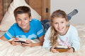 Kids playing with smartphone on a bed Royalty Free Stock Photo
